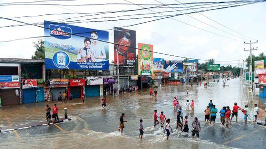 Sri Lankan residents make their way through floodwaters in Kaduwela