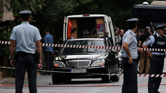 Police secure the area around the car of former Greek prime minister Lucas Papademos following the detonation of an envelope injuring him and his driver, in Athens, Greece, May 25, 2017.
