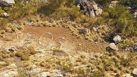 Police are trying to find whoever made the SOS symbol out of rocks