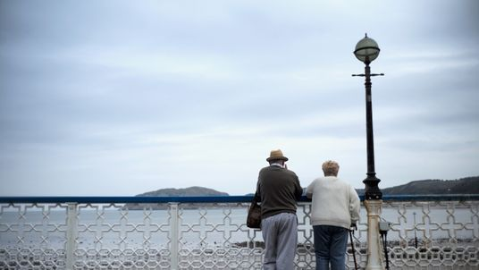 LLANDUDNO, WALES - SEPTEMBER 08: Senior citizens walk along Llandudno Pier on September 8, 2014 in Llandudno, Wales. Britain is facing multiple problems stemming from an increase in the elderly proportion of its population, including increasing health care costs, strains on its social security system, a shortage of senior care workers and challenges to the employment market