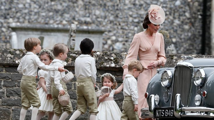 Kate holds Charlotte's hand as she tries to marshal the page boys and bridesmaids into a classic car