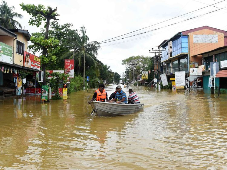 Sri Lankan residents travel by boat through floodwaters in Kaduwela