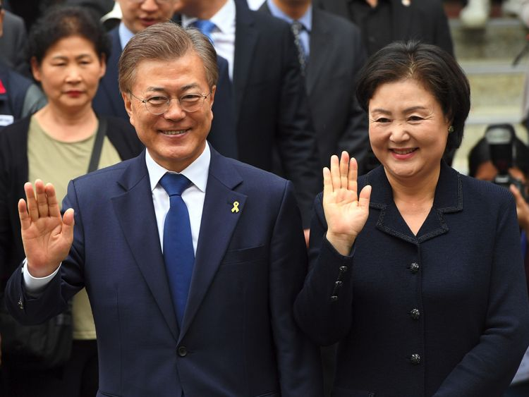 Mr Moon and his wife pose for the cameras after voting