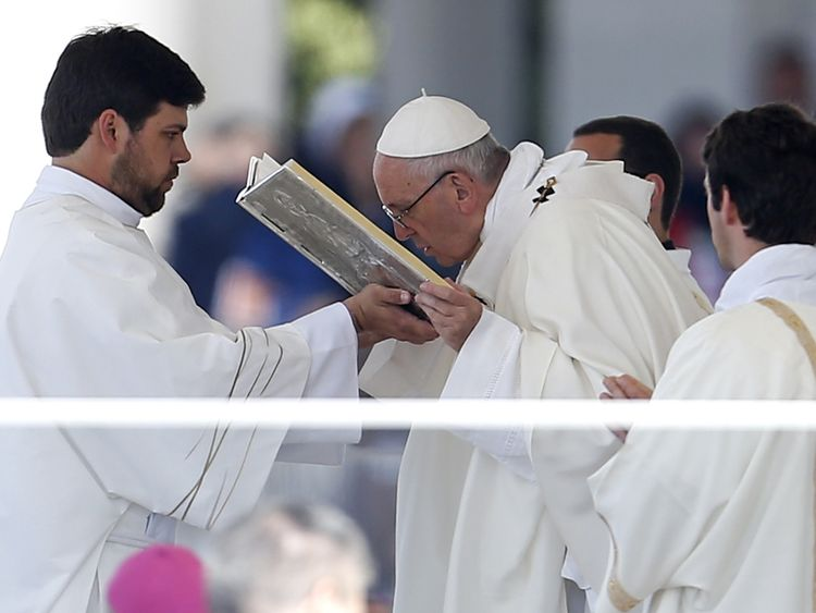 Pope Francis kisses the book of the gospels as he leads the Holy Mass at the Shrine of Our Lady of Fatima