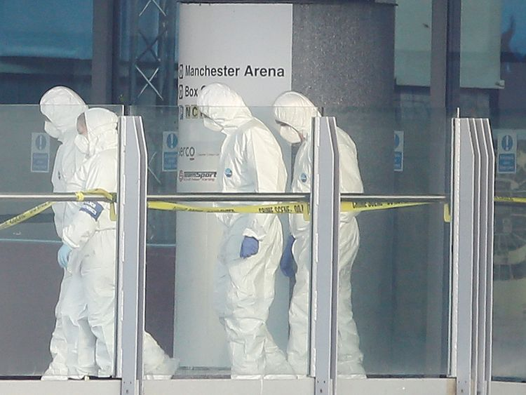 Forensics investigators work at the entrance of the Manchester Arena