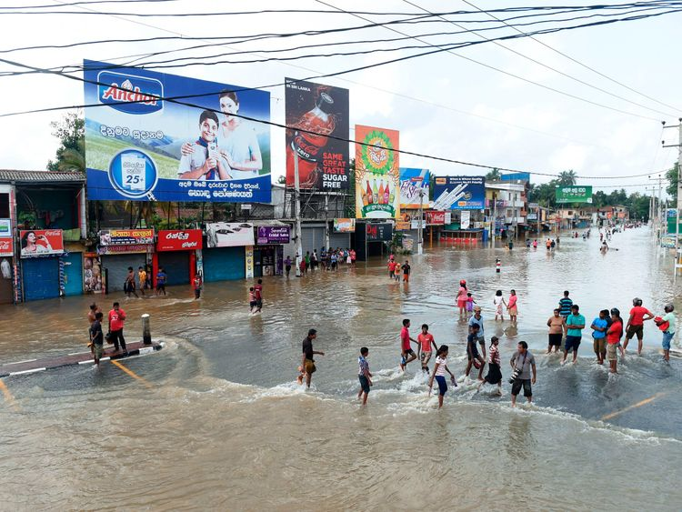 Sri Lankan residents make their way through floodwaters in Kaduwela