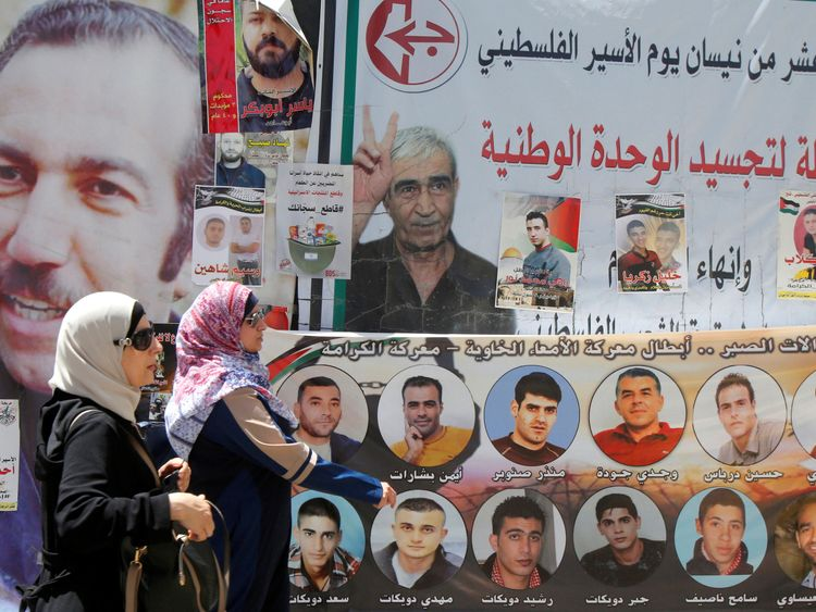 Women walk past images of Palestinian prisoners on hunger strike in Israeli jails