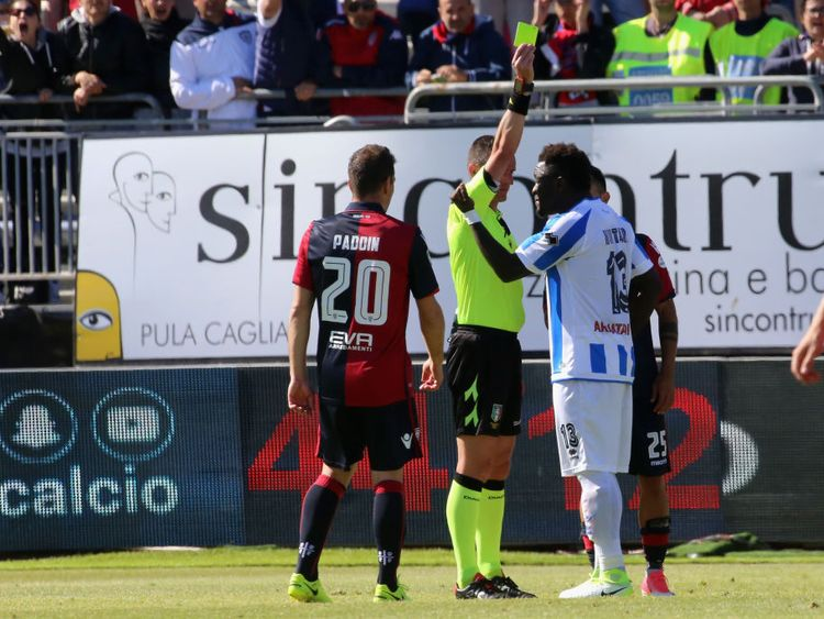 Sulley Muntari is booked after remonstrating with the fans