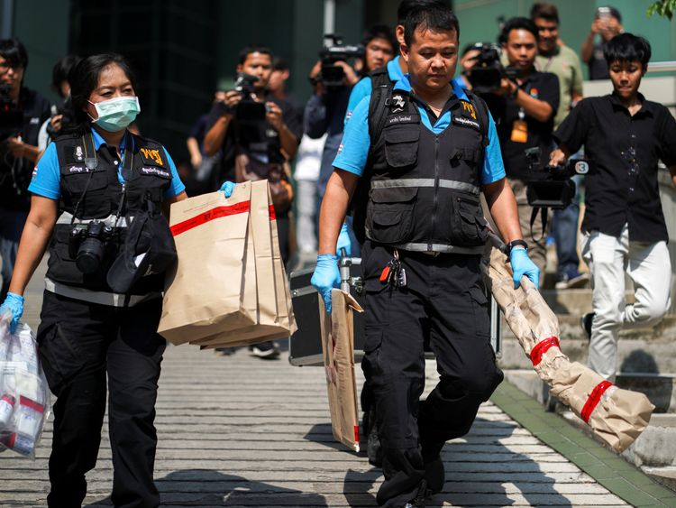 Forensic police carry evidence away from the scene of the explosion in Bangkok