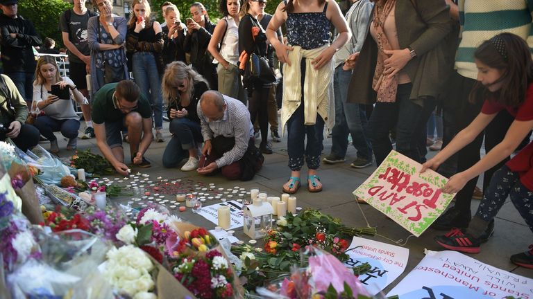 People pile up flowers and arrange candles in tribute to those who have died