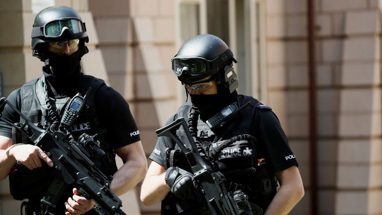 Armed police officers near to where a man was arrested in the Chorlton area of Manchester