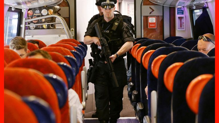 Firearms officers with the British Transport Police disembark trains at London Euston.