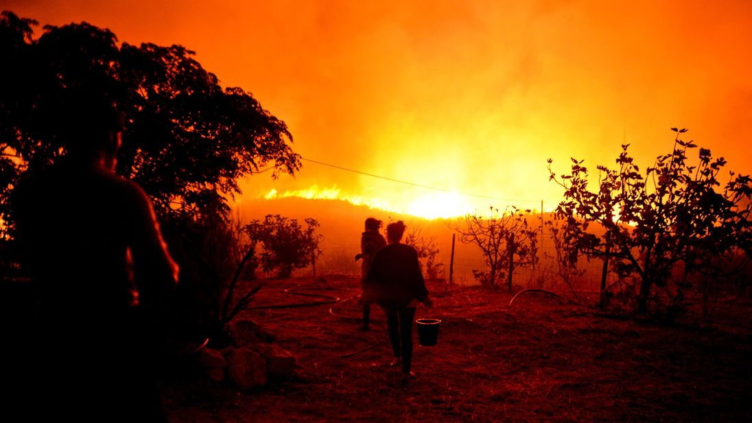 A woman carries a bucket of water as a wildfire nears her house at Monchique, Algarve