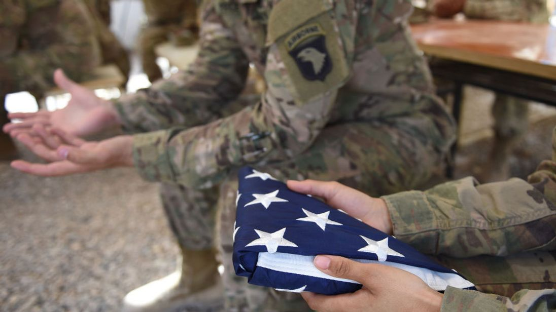 A US soldier holds the national flag in Lashkar Gah in the Afghan province of Helmand