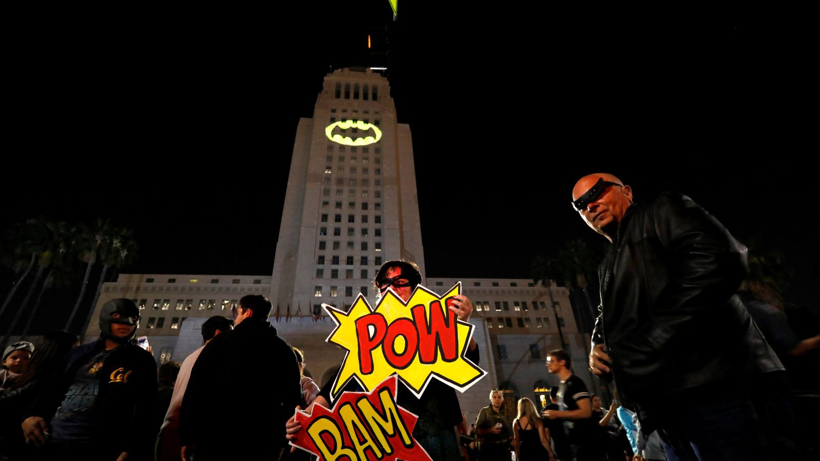 Enthusiasts pose as a bat-signal is projected on City Hall in honour of late actor Adam West in Los Angeles, California