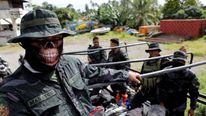 Members of the Philippine National Police Special Action Force ride on a truck in Iligan