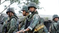 Philippine soldiers ride on a military vehicle