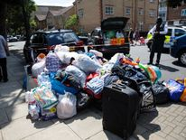 A pile of donated clothes, sleeping bags and water near Grenfell Tower