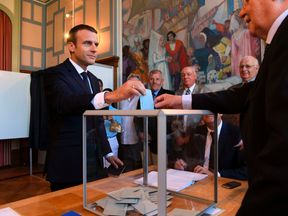 French President Emmanuel Macron casts his ballot as he votes at a polling station in Le Touquet, northern France, during the second round of the French parliamentary elections (elections legislatives in French), on June 18, 2017. / AFP PHOTO / POOL / CHRISTOPHE ARCHAMBAULT (Photo credit should read CHRISTOPHE ARCHAMBAULT/AFP/Getty Images)