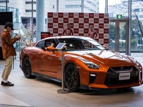 A visitor poses next to a Nissan GTR in Yokohama, Japan
