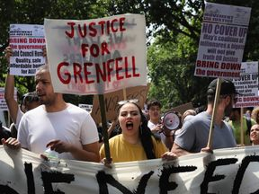 Protesters hold signs calling for 'justice' for the victims of the Grenfell Tower fire