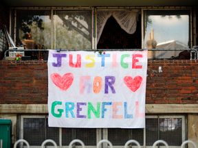 A poster hangs outside a building calling for 'Justice for Grenfell', justice for victims of the June 14 Grenfell Tower block fire, in Kensington, west London, on June 17, 2017