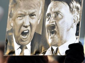 A protester holds up a poster depicting US President Donald Trump and German dictator Adolf Hitler