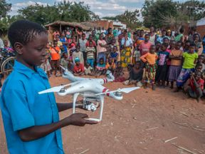 A child holds a drone during a drone awareness and safety demonstration on June 22, 2017, in regards to humanitarian drone corridor testing under the UNICEF-funded Humanitarian Drone Corridor testing project, in the hard-to-reach rural Chanthunthu Village Health Clinic in Kasungu