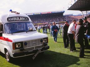 Injured Liverpool fans are carried over to an ambulance on the field by the police