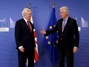 Michel Barnier offers his hand to Brexit Secretary David Davis as negotiations start in Brussels