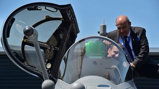 France's President Emmanuel Macron (C) sits in a Dassault Aviation Rafale fighter jet as Dassault Aviation CEO Eric Trappier (R) looks on during the International Paris Air Show in Le Bourget outside Paris on June 19, 2017