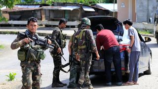 Philippine National Police Special Action Force personnel man a checkpoint in Marawi city
