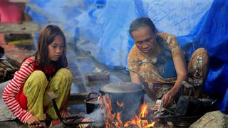 Evacuees cook food in a open area of the evacuation centre at Saguiran village in Lanao Del Sur