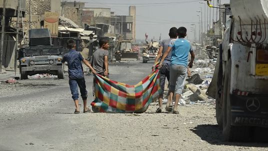 Boys in west Mosul carrying their possessions in a rug