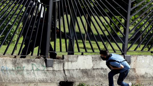 A member of the riot security forces points a gun through the fence at an opposition supporter during clashes at a rally against Venezuelan President Nicolas Maduro's government in Caracas, Venezuela June 22, 2017. REUTERS/Carlos Garcia Rawlins