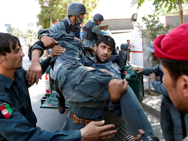 An injured police officer is carried from the protests in Kabul