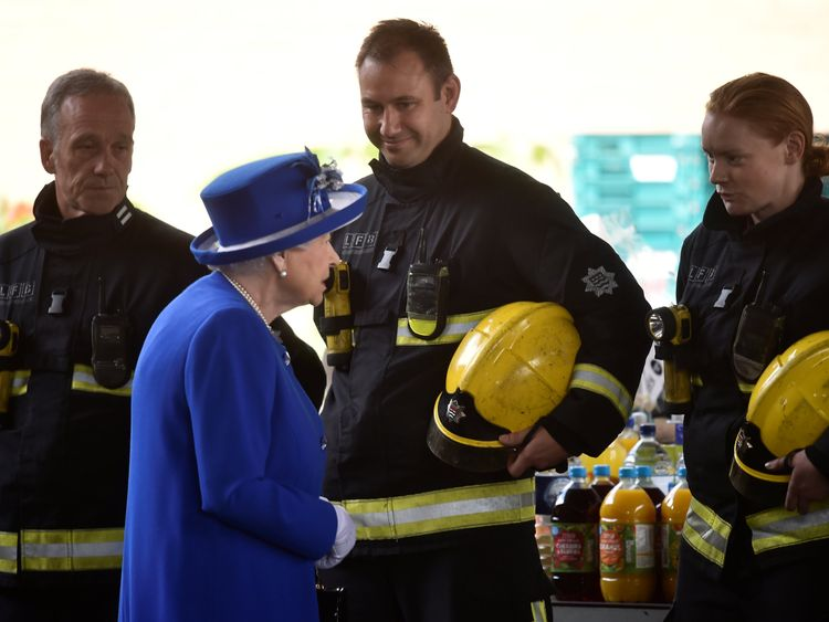 Queen Elizabeth meets firefighters near the scene of the the fire that destroyed the Grenfell Tower block