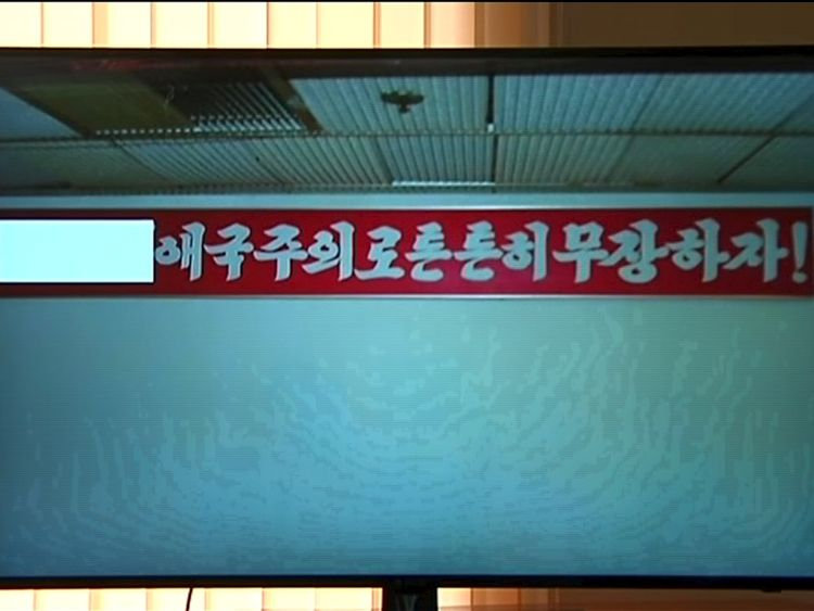 The propaganda sign Mr Warmbier attempted to take from his hotel