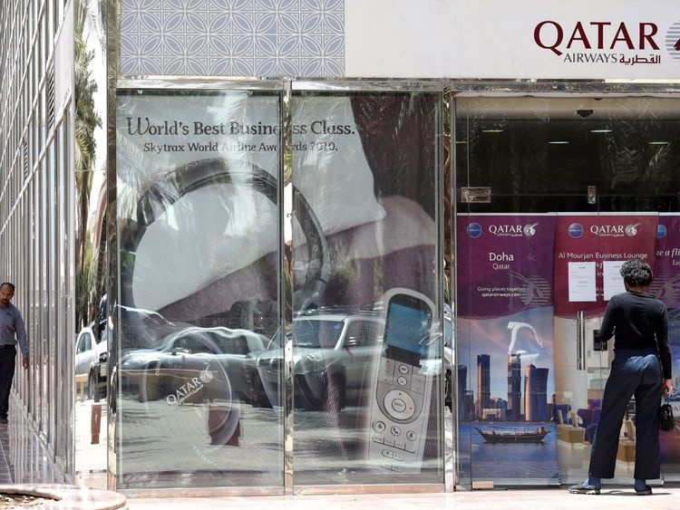 A man stands outside a closed Qatar Airways branch in Saudi Arabia's capital, Riyadh