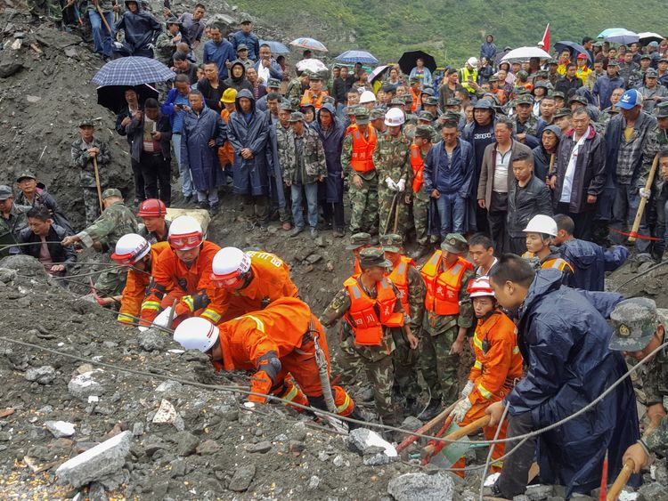 People search for survivors at the site of a landslide in Xinmo Village, Mao County, Sichuan province, China June 24, 201