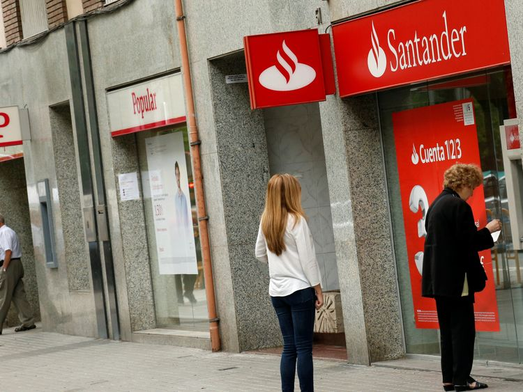 People use a Santander's cash dispenser (ATM) as a man leaves a Banco Popular office in Barcelona