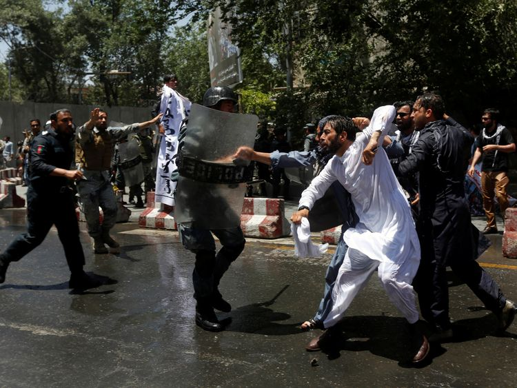 Riot police clash with people protesting about a huge bomb attack in Kabul
