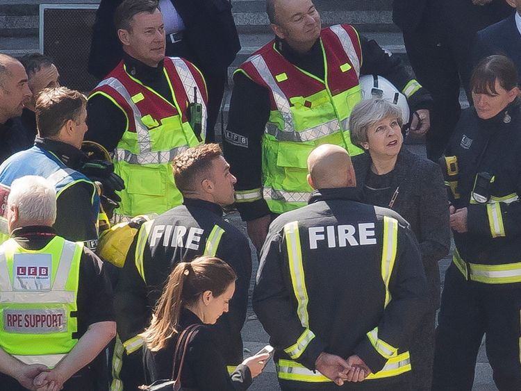 Theresa May is briefed by the emergency services at the scene in north Kensington