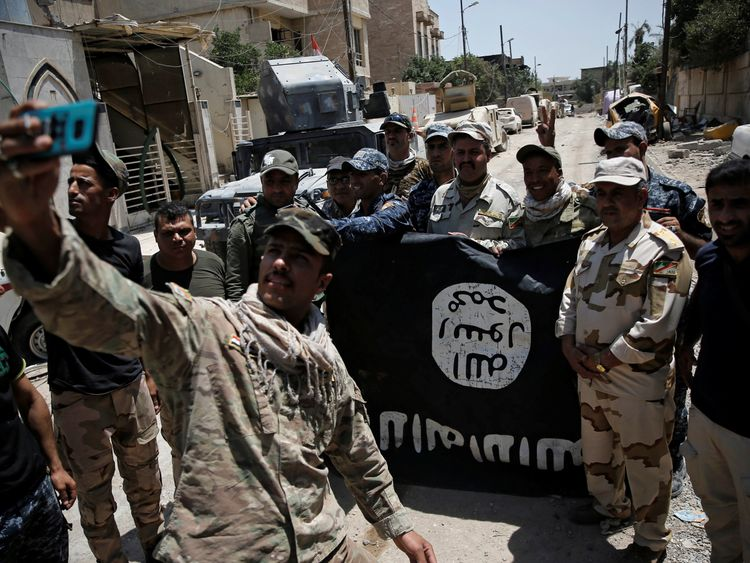 Iraqi troops with a captured Islamic State flag