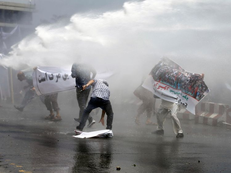 Protesters are hit by a water cannon in the capital