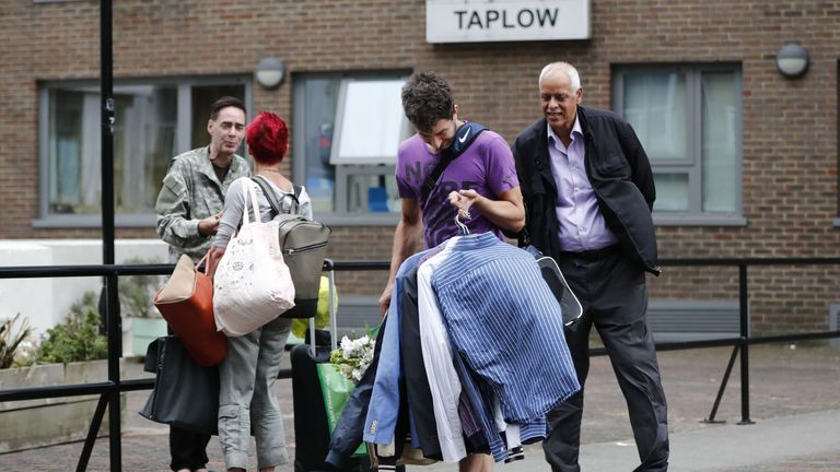 A man carrying shirts leaves Taplow Tower residential block on the Chalcots Estate in north London