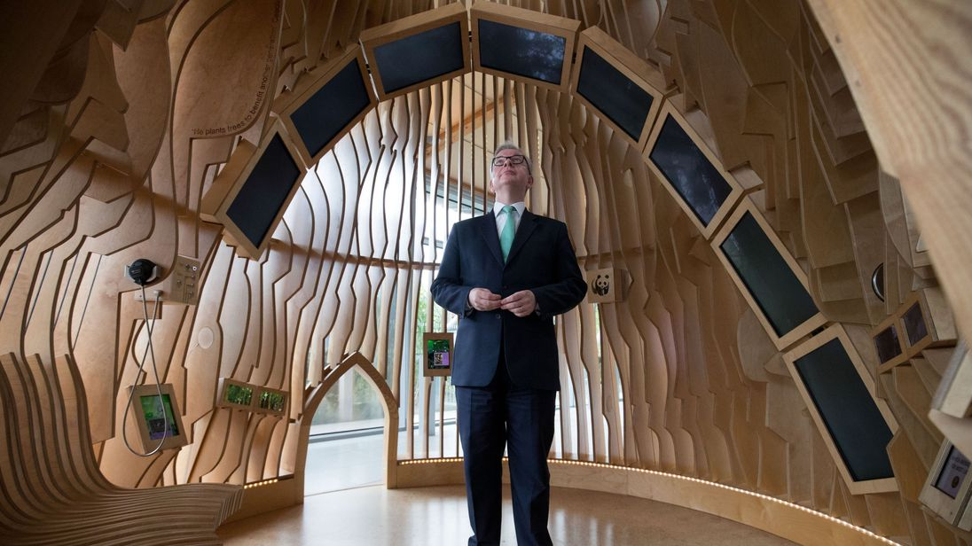 Environment Secretary Michael Gove looks at screens in the information pod in the forest zone at the WWF Living Planet Centre