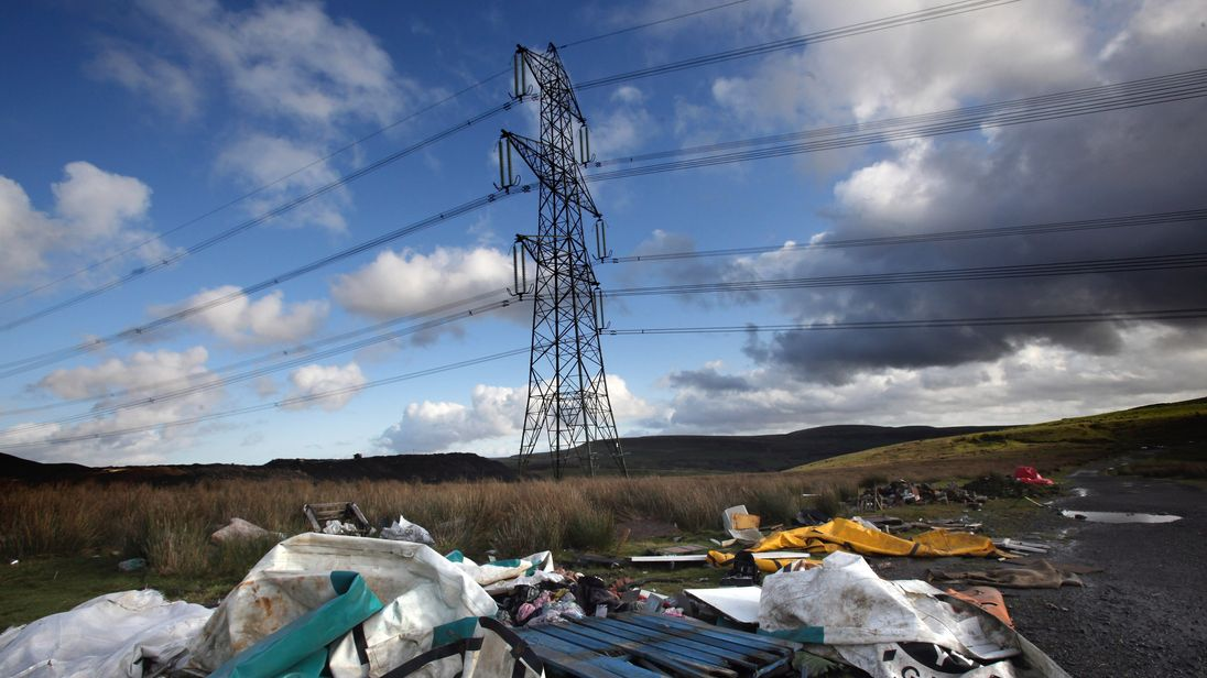 Dumped and fly tipped rubbish litters the ground beneath electricity pylons passing the Ffos-Y-Fran opencast coal mine on November 17, 2009 in Merthyr Tydfil, Wales