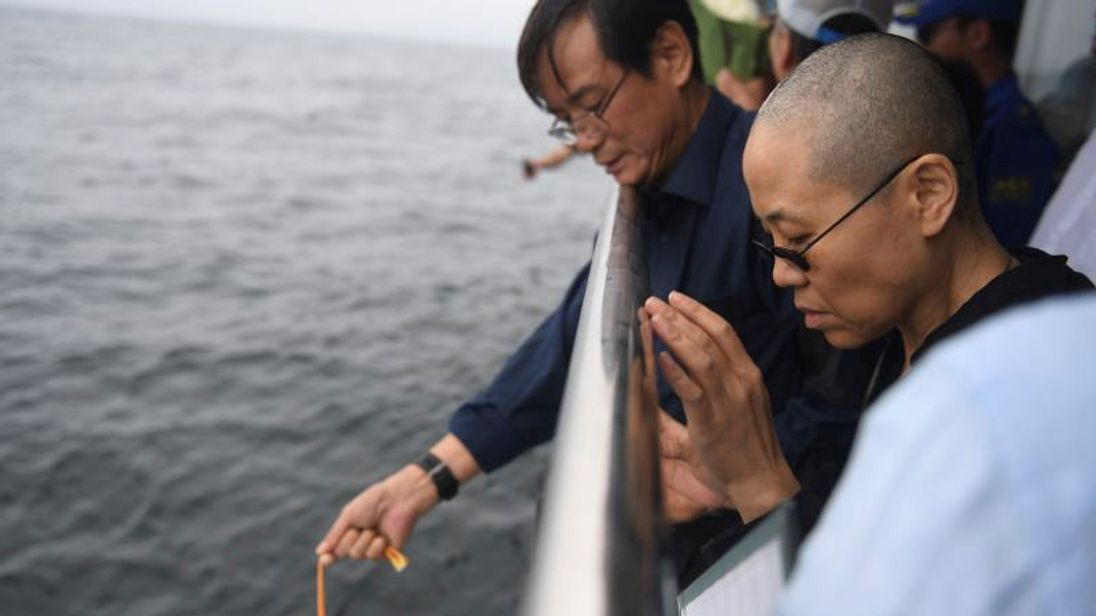 Ms Liu and other relatives lower the ashes into the sea