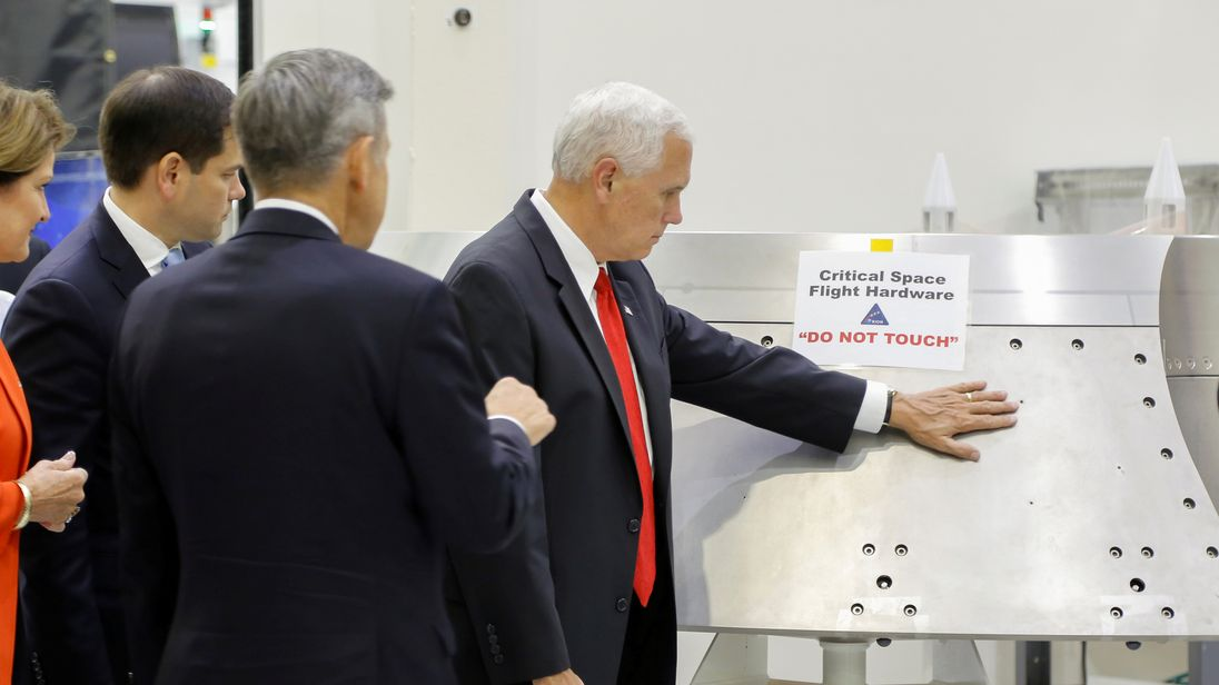 """U.S. Vice President Mike Pence touches a piece of hardware with a warning label """"Do Not Touch"""" next to Kennedy Space Center Director Robert Cabana during a tour of the Operations and Checkout Building in Florida July 6, 2017. Picture taken July 6, 2017"""